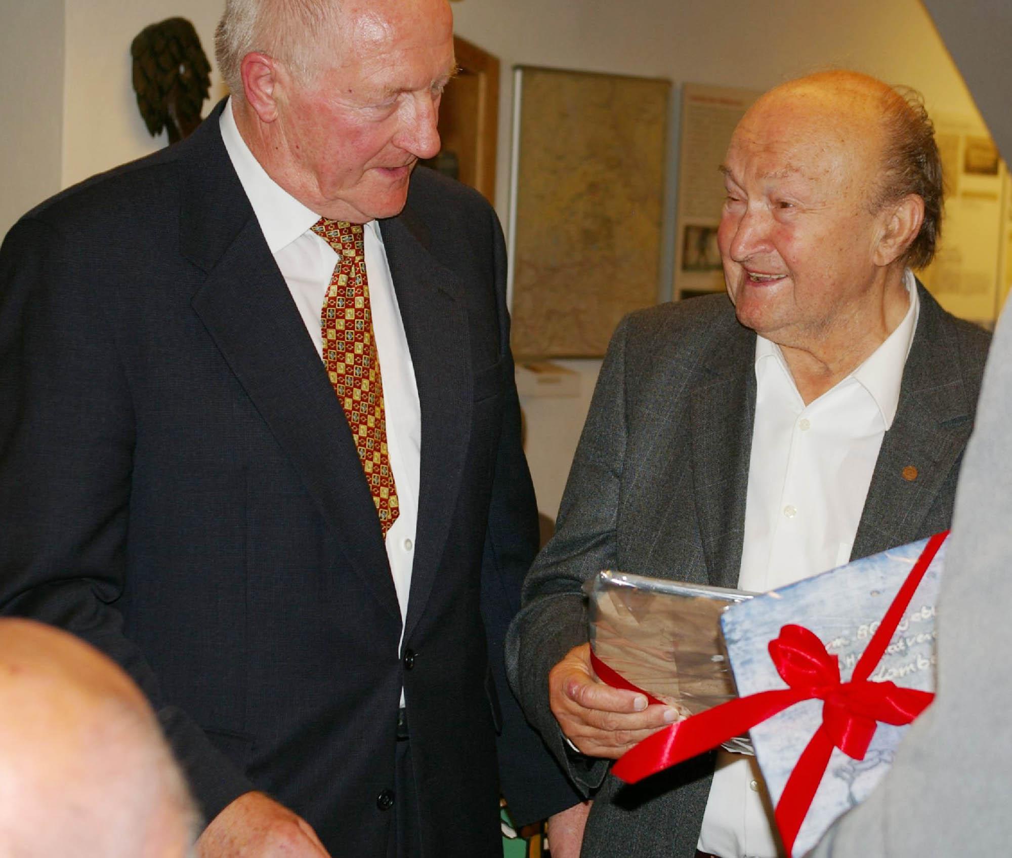 Günter Knaus erhält ebenso wie Lambert Grasmann als Geburtstagsgeschenk aus der Hand des Vorsitzenden eine speziell für die jeweilige  Tätigkeit gestaltete Keramikplatte.